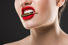 Cropped view of aggressive woman holding bullet in teeth. Isolated on grey stock images