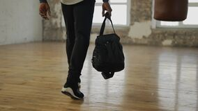 Cropped view of an athlete walking into room with a bag, ready to start training