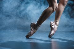 Cropped view of ballerina dancing in pointe shoes in dark studio. With smoke royalty free stock images