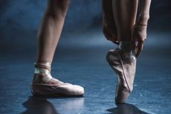 Cropped view of ballet dancer in pointe shoes. In dark studio stock images