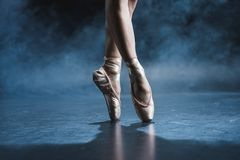 cropped view of ballet dancer in pointe shoes in dark studio royalty free stock photos