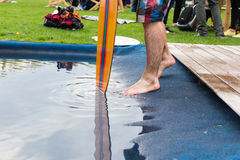 Cropped view of barefoot person wading in pool. At event near standing spectators Stock Image