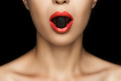 Cropped view of beautiful naked woman with black jelly candy in mouth. Isolated on black Royalty Free Stock Photography