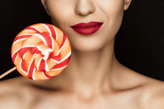 Cropped view of beautiful naked woman with red lips holding lollipop. Isolated on black Royalty Free Stock Photography