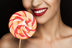 Cropped view of beautiful naked woman with red lips holding lollipop. Isolated on black Stock Images