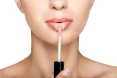 Cropped view of beautiful woman applying pink lipgloss on lips,. Isolated on white Royalty Free Stock Images