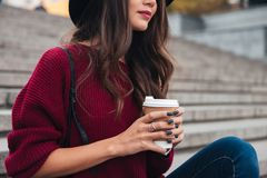 Cropped view of brunette woman in hat and sweater. Sitting on stairs outdoors with cup of coffee Royalty Free Stock Image
