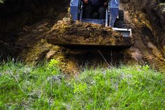 Cropped view of bulldozer loaded with soil in dirty pit with grass on foreground royalty free stock images