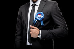 Cropped view of businessman in black suit with vote badge. Isolated on black Stock Images