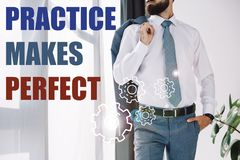 cropped view of businessman standing near window with practice makes perfect lettering royalty free stock photography