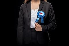 Cropped view of businesswoman in black suit with vote badge. Isolated on black Stock Photos