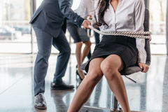 Cropped view of businesswoman bound with rope on chair and businesspeople pulling her Stock Image