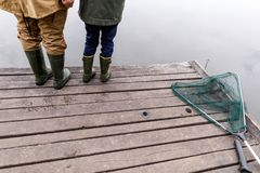 Father and son fishing together. Cropped view of father and son fishing together with rods on wooden pier at lake Royalty Free Stock Photo