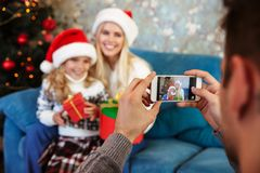 Cropped view of father taking photo of his wife and daughter in stock image