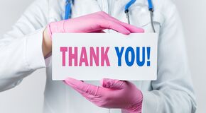 Cropped view of female doctor in a white coat and pink sterile gloves holding a card with words - Thank you