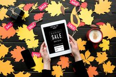 Digital tablet with blank screen. Cropped view of female hands with digital tablet with blank screen on table with autumn leaves, coffee and sale tags stock illustration