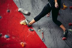 Beautiful young strong woman climbing on red artificial wall top view. royalty free stock photo