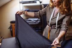 Female tailor choosing fabric for pattern cutting. Men`s Wear industry, tailoring process Concept royalty free stock photo