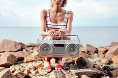 Cropped view of girl posing with vintage boombox. On rocky shore royalty free stock images