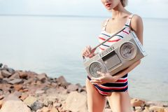 Cropped view on girl in striped swimsuit posing with vintage boombox. On rocky beach stock image