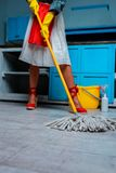 Housewife mopping floor. Cropped view of housewife mopping floor in kitchen Royalty Free Stock Image