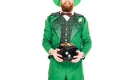 Cropped view of leprechaun in green suit holding pot of gold. Isolated on white Royalty Free Stock Image