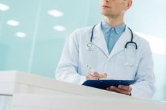 Cropped view of male doctor in white coat with stethoscope writing diagnosis. In hospital royalty free stock photography