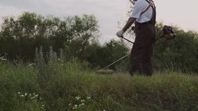 Cropped view of male gardener using electric trimmer. Cropped view of male gardener in overalls using electric trimmer and cutting grass in park. Man working and stock footage