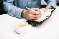 Male hands with coffee cup writing in diary. Cropped view of male hands with coffee cup writing in diary Stock Image
