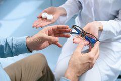 Cropped view of man choosing eyeglasses or contact lenses. In optical clinic royalty free stock photography