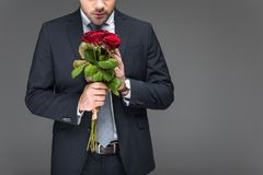 Cropped view of man holding bouquet of red roses,. Isolated on grey royalty free stock photography