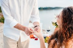 Cropped view of man wearing ring on womans finger after propose on romantic. Date stock photo