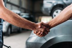 cropped view of mechanics shaking hands in auto stock illustration