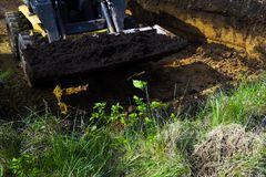 Cropped view of messy bulldozer with soil in its bucket during excavation works. Industrial machine making foundation pit for new house. machinery, industry stock images