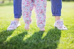 Cropped view of mother supporting baby daughter and helping her make first steps royalty free stock image