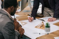 Cropped view of multiethnic architects discussing and drawing blueprints. In modern office stock photos
