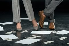 Cropped View Of Businesspeople Standing On Floor With Documents And Dollar Banknotes, Royalty Free Stock Photo