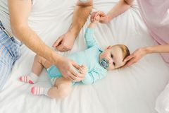 Cropped view of parents playing with baby daughter royalty free stock images