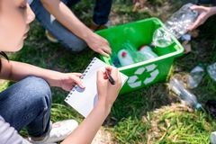 Cropped view of people cleaning park with green recycling box and writing. In textbook royalty free stock image