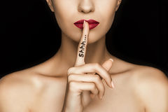 Cropped view of seductive woman with red lips showing shh symbol. Isolated on black stock photography