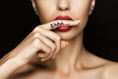Cropped view of seductive woman with red lips showing shh symbol. Isolated on black royalty free stock images