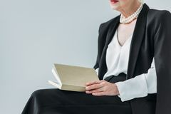 Cropped view of senior lady with pearl necklace holding book,. Isolated on grey stock photos