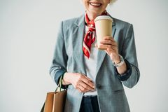 Cropped view of senior woman in jacket and sunglasses with shopping bags and coffee,. Isolated on grey royalty free stock photo