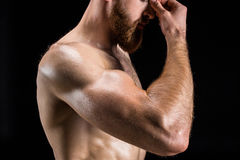 Cropped view of shirtless bearded bodybuilder posing isolated on black. In studio Stock Image