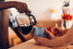 cropped view of smiling african american barista pouring coffee into cups on bar counter stock images