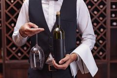 Cropped view sommelier holding bottle of wine and glass. In cellar stock photo