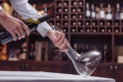Cropped view sommelier pouring red wine from bottle into decanter at table. In cellar royalty free stock images