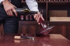 Cropped view sommelier pouring red wine from bottle into decanter at table. In cellar royalty free stock photography