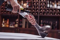 Cropped view sommelier pouring red wine from bottle into decanter at table. In cellar royalty free stock photo