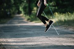 cropped view of sportswoman jumping on skipping rope stock photo